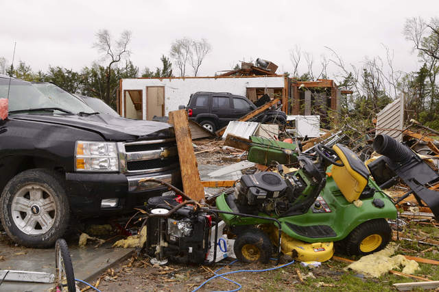 Smashed cars and belongings litter the surroundings of a house in Cordova, Neb., on Monday, May 12, 2014, after several tornadoes moved across Nebraska on Sunday causing damage to homes and busine ...