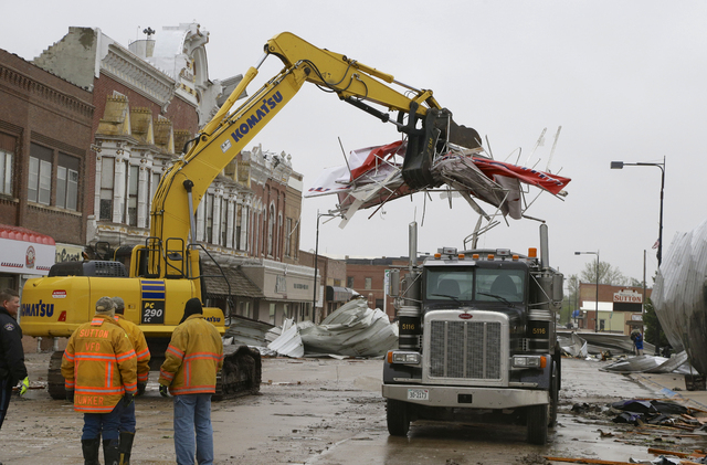 Debris is cleared from downtown Sutton, Neb., Monday, May 12, 2014, after a tornado touched down in town on Sunday. Several tornadoes moved across Nebraska on Sunday causing damage to homes and bu ...
