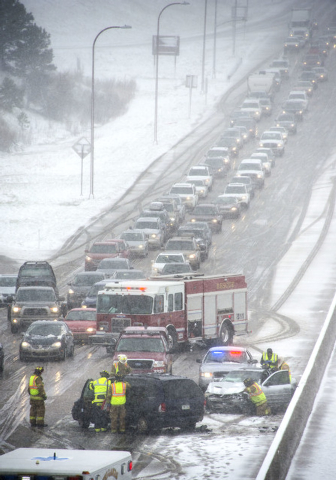 Firefighters work the scene of a two-car injury accident that was one of many that slowed traffic on Interstate 25 north of Colorado Springs, Colo., as a spring snowstorm swept through the state o ...