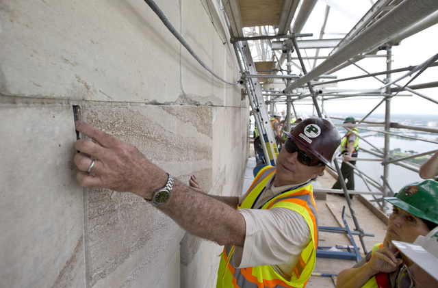 Bob Collie, project manager with Perini Management Services, puts his finger in a crack of the Washington Monument at the 491-foot level of the scaffolding surrounding the monument on June 2, 2013 ...