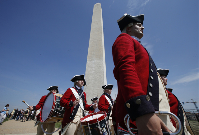 Members of the United States Army Old Guard Fife and Drums Corps march beneath the Washington Monument in Washington on Monday, May 12, 2014, during a ceremony to celebrate its reopening. The monu ...