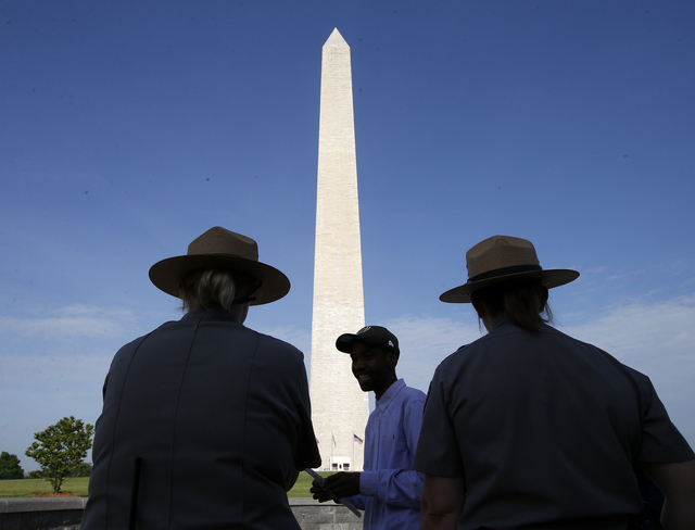 Park Service employees stand watch as visitor Roman Tanner, center, walks away with his Washington Monument ticket, which are distributed at on a first-come basis at the Washington Monument in Was ...