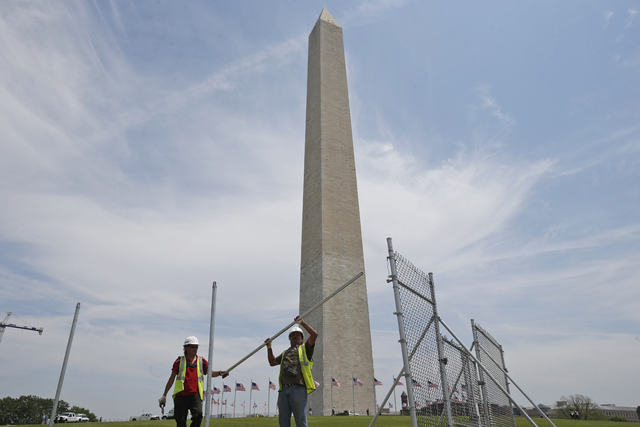 Workers Julio Dichis, right, and Jose Oreyana on Friday, May 9, 2014, remove the fencing that closed the Washington Monument off to the public during renovations Washington. The monument, which su ...