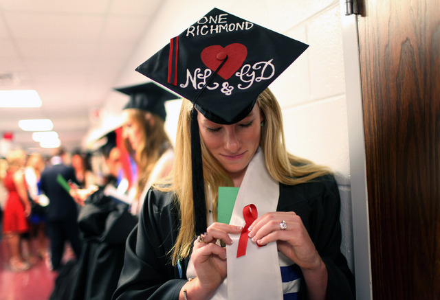 Laura Jordan wears a red ribbon with her hat decorated with initials of Natalie Lewis and Ginny Doyle before the University of Richmond's Commencement Ceremony in Richmond, Va. on Sunday, May 11,  ...