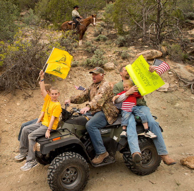 As a Kane County sheriff's deputy watches from a horse, ATV riders make their way into Recapture Canyon, north of Blanding, Utah, on Saturday, May 10, 2014, in a protest against what demonstrators ...