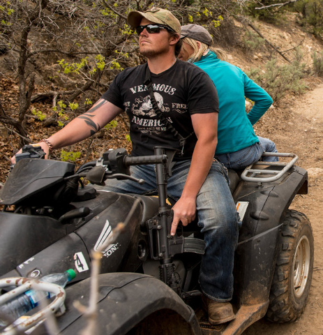 An ATV rider holds his finger near the trigger of his assault rifle as he and others make their way into Recapture Canyon, north of Blanding, Utah, on Saturday, May 10, 2014, in a protest against  ...