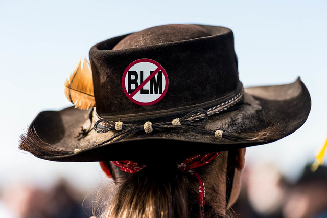 A protester, wearing an anti-Bureau of Land Management sign on his hat, listens to San Juan County Commissioner Phil Lyman at Centennial Park in Blanding, Utah on Saturday, May 10, 2014. Lyman org ...