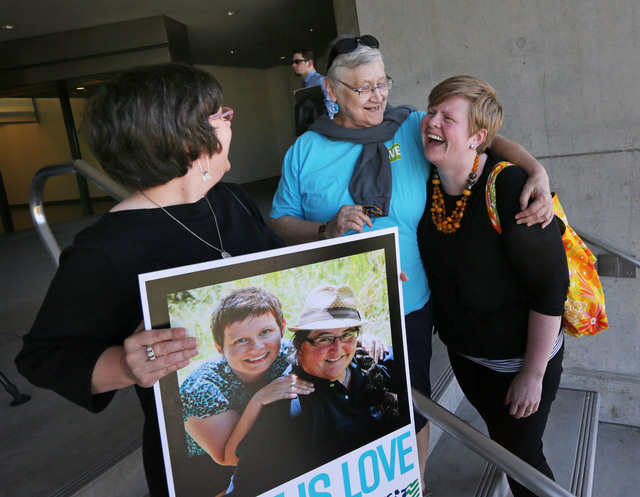 Victoria Smith Weiland, left, from Eugene, Ore., holds a picture of her and her partner Peggy McComb, as McComb hugs Aubrey Chonbold, right, on the steps of the Wayne L. Morse U.S. Courthouse Wedn ...