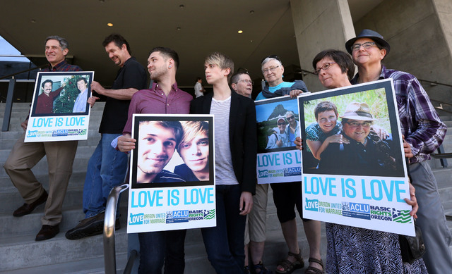 Supporters of same-sex marriage hold photos of themselves and their family members or partners on the steps of the Wayne L Morse U.S. Courthouse Wednesday, May 14, 2014, in Eugene, Ore. A federal  ...
