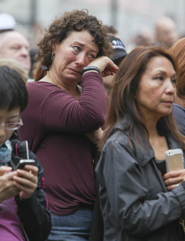 Visitors stand on the memorial plaza to view the program on a television monitor during the dedication ceremony at the National September 11 Memorial Museum in New York, Thursday, May 15, 2014.  ( ...