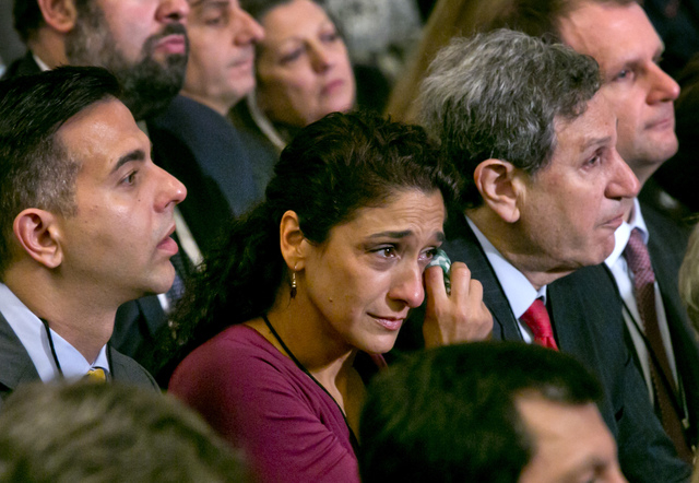 A woman in the audience dries a tear during the dedication ceremony in Foundation Hall, of the National September 11 Memorial Museum, in New York, Thursday, May 15, 2014. (AP Photo/Richard Drew, Pool)