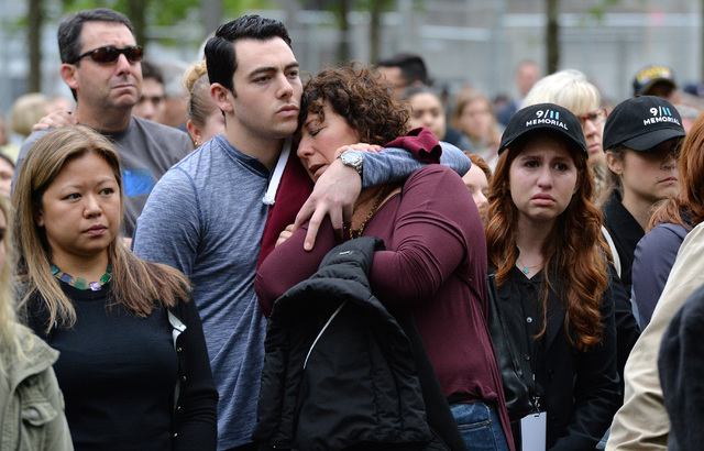 Two people embrace while gathered on the plaza of the National September 11 Memorial to watch the telecast of the dedication ceremony at the National September 11 Memorial Museum in New York on Th ...