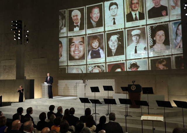 Former New York Gov. George Pataki speaks as photos of 9/11 victims are projected, during the dedication ceremony in Foundation Hall, of the National September 11 Memorial Museum, in New York, Thu ...
