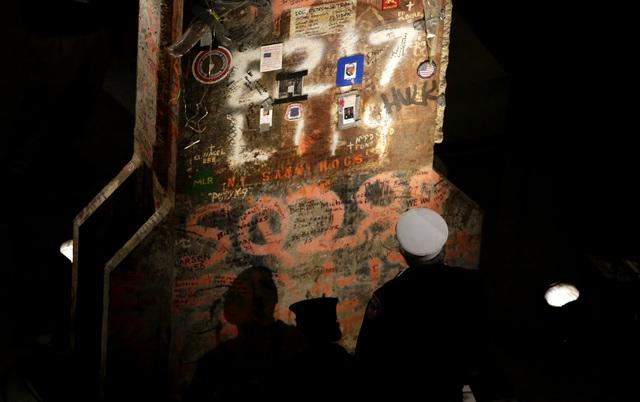 A New York City firefighter looks at the last column recovered at the World Trade Center site at the dedication ceremony for the National 9/11 Memorial Museum on Thursday, May 15, 2014 in New York ...