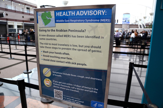 This May 14, 2014 image, provided by Denver International Airport, shows newly-erected signs warning travelers about he danger of the MERS virus, at Denver International Airport. MERS, or Middle E ...