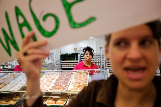 Krispy Kreme employee Beverly Ford, rear, looks on as demonstrators enter the store during a protest, Thursday, May 15, 2014, in Atlanta. Calling for higher pay and the right to form a union witho ...