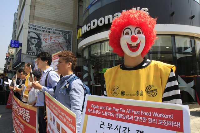 A protester dressed as Ronald McDonald participates in a rally to demand higher wages for fast-food workers outside a McDonald restaurant in Seoul, South Korea, Thursday, May 15, 2014. About 30 la ...