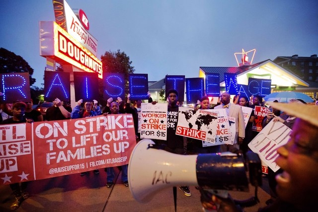 McDonald's employee Connie Ogletree, 55, right, leads a group of fast food workers and supporters in a chant during a protest outside a Krispy Kreme store, Thursday, May 15, 2014, in Atlanta. Call ...