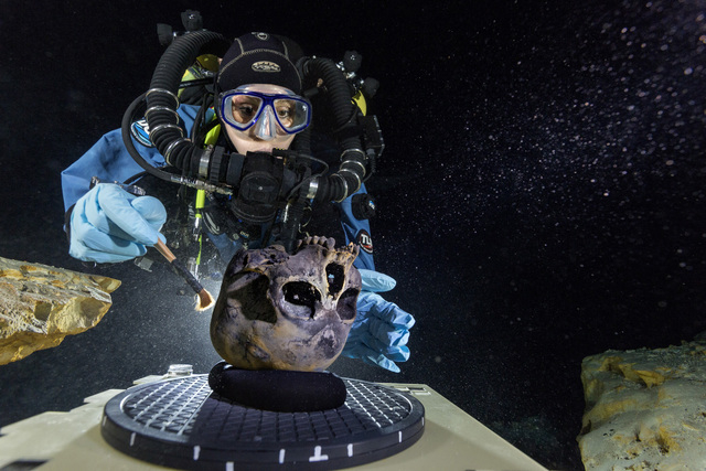 Diver Susan Bird, working at the bottom of Hoyo Negro in 2013, a large dome-shaped underwater cave in Mexico's Yucatan Peninsula, brushes a human skull found at the site while her team members tak ...