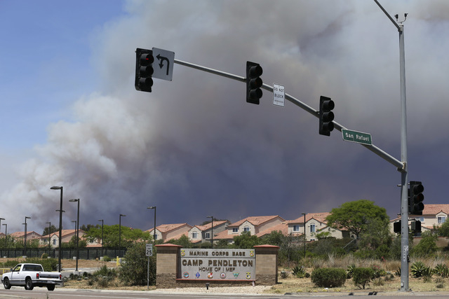 Smoke plumes rise behind the  Marine Corps Camp Pendleton entrance Friday, May 16, 2014, in Oceanside, Calif. San Diego County officials said Friday five wildfires have been 100 percent contained. ...