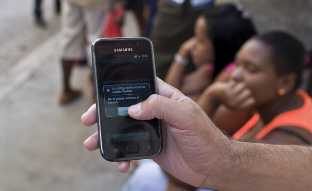 """A cellphone owner shows the screen on his phone that reads in Spanish; """"The configuration has not been able to finish. Cannot connect to server.,"""" as he tries to connect to the Etecsa server while ..."""