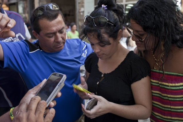 In this May 9, 2014 photo, people try to connect to the Etecsa server as they wait with other customers outside the offices of the state telecom monopoly Etecsa in Havana, Cuba. Cubas government b ...