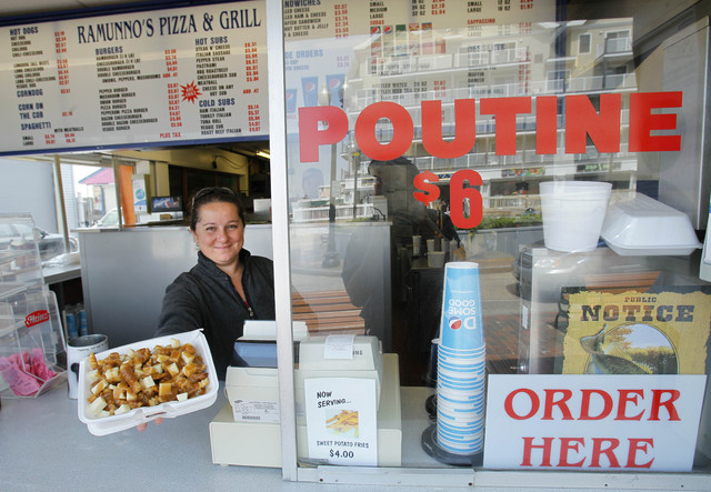 FILE - In this May 26, 2011, file photo, Karen Ramunno of Ramunno's Pizza and Grill, delivers an order of poutine, a french fry, gravy and cheese dish popular with Canadians, at Old Orchard Beach, ...