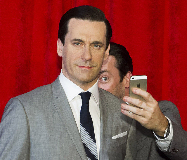 FILE - This May 9, 2014, file photo, shows actor Jon Hamm, right, taking a selfie at the unveiling of his wax figure at Madame Tussauds in New York. Selfie is one of the 150 new words appearing in ...