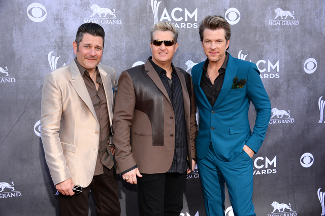FILE - In this April 6, 2014 file photo, from left, Jay DeMarcus, Gary LeVox and Joe Don Rooney, of the musical group Rascal Flatts, arrive at the 49th annual Academy of Country Music Awards at th ...