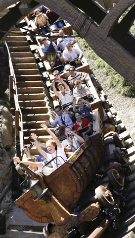 This May 16, 2014 photo shows Disney castmembers testing the new Seven Dwarfs Mine Train roller coaster in the Magic Kingdom at Walt Disney World, in Lake Buena Vista, Fla. The ride will be open t ...