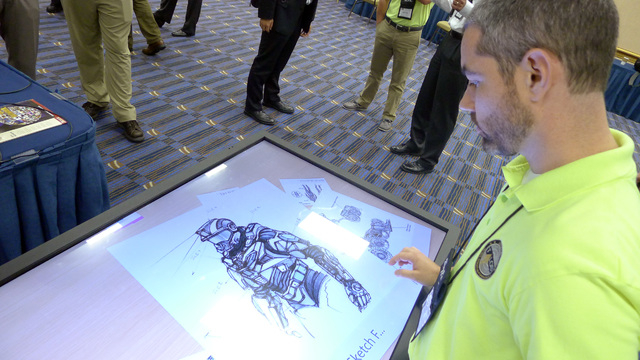 Michael Fieldson , the civilian project manager for the Tactical Assault Light Operator Suit at McDill Air Force Base, looks at sketches of the body armor exoskeleton during the Special Operations ...