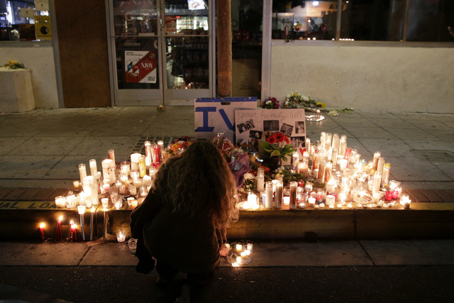 A woman places a candle in front of IV Deli Mart, where par of Friday night's mass shooting took place by a drive-by shooter, on Saturday, May 24, 2014, in the beach community of Isla Vista, Calif ...