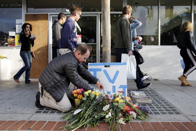 Stephen Nichols arranges flowers left in front of IV Deli Mart, where part of Friday night's mass shooting took place by a drive-by shooter, on Saturday, May 24, 2014, in Isla Vista, Calif. Sherif ...