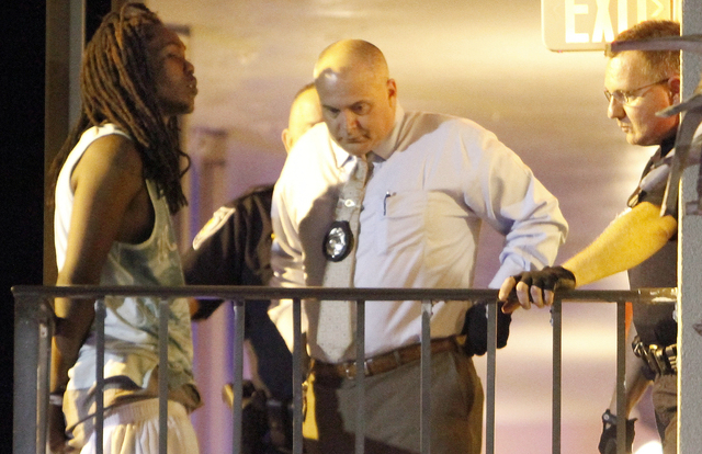 A man is handcuffed as he talks to police at the scene of a shooting that left three people dead at Bermuda Sands Resort late Saturday, May 24, 2014. Police report three people were killed and one ...