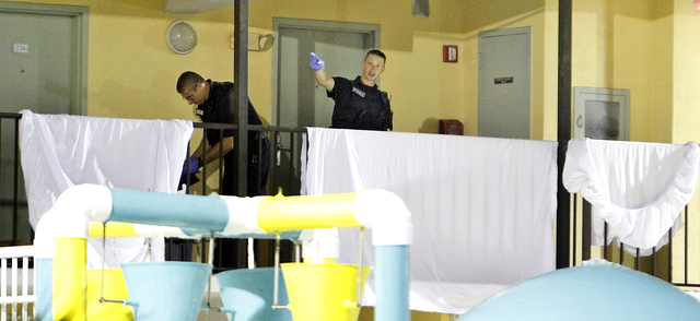 Myrtle Beach Police investigate where two bodies are behind the sheets on the walkway that's over a water park in front of the Bermuda Sands Resort late Saturday, May 24, 2014. Police report three ...