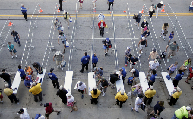 Fans make their way though a security checkpoint as they enter the Indianapolis Motor Speedway before the start of the 98th running of the Indianapolis 500 IndyCar auto race in Indianapolis, Sunda ...