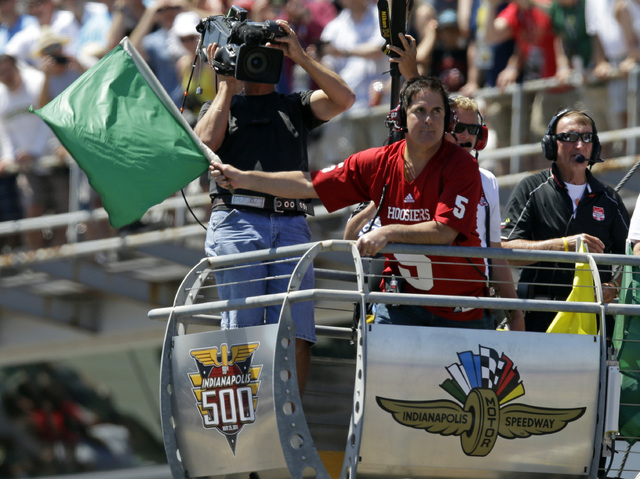 Dallas Mavericks owner Mark Cuban waves the green flag to start the 98th running of the Indianapolis 500 IndyCar auto race at the Indianapolis Motor Speedway in Indianapolis, Sunday, May 25, 2014. ...