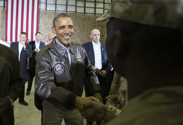 President Barack Obama shakes hands during a troop rally at Bagram Air Field, north of Kabul, Afghanistan, during an unannounced visit on Sunday, May 25, 2014. (AP Photo/ Evan Vucci)