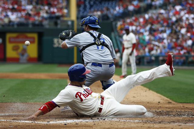 Philadelphia Phillies' Cesar Hernandez, bottom, scores past Los Angeles Dodgers catcher A.J. Ellis on a single by Ben Revere during the second inning of a baseball game, Saturday, May 24, 2014, in ...