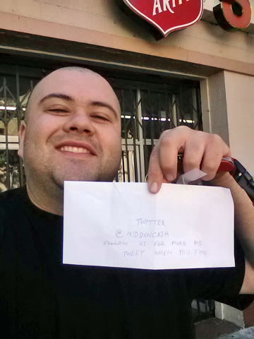 This image provided by Sergio Loza shows Loza holding up an envelope that had cash hidden in it in San Francisco, on Sunday, May 25, 2014. Loza followed the clues from a Twitter user using the han ...