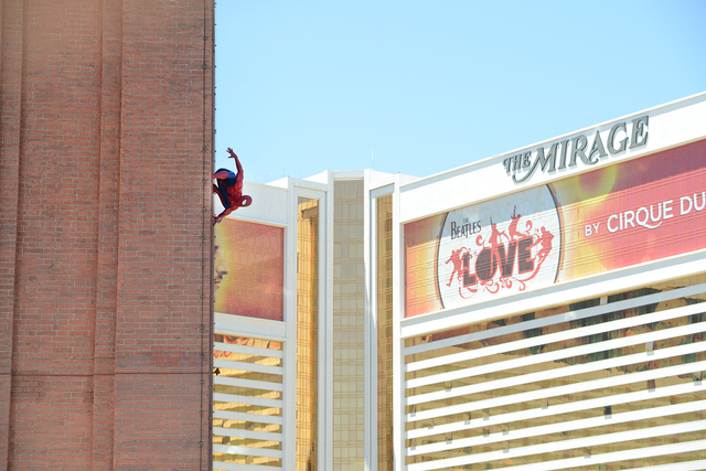 In this photo provided by the Las Vegas News Bureau, a life-size Spider-Man wax figure produced by Madame Tussauds hangs on The Venetian's campanile tower in Las Vegas Friday, May 02, 2014. ...