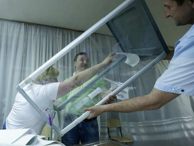 Members of the election commission empty ballot boxes in a polling station in Kiev May 25, 2014.  Billionaire Petro Poroshenko claimed Ukraine's presidency on Sunday after exit polls gave him an a ...
