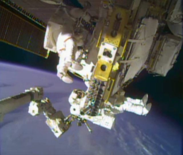 In this image taken from video provided by NASA, astronauts Rick Mastracchio, top, and Michael Hopkins work to repair an external cooling line on the International Space Station on Monday, Dec. 24 ...