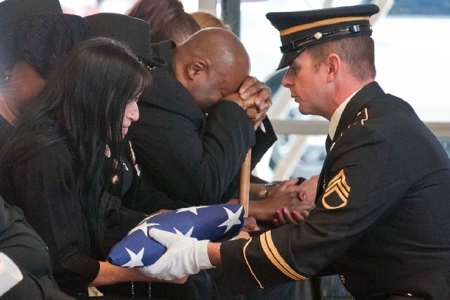 "Stanley Gibson''s widow, Rondha Gibson, receives the flag from his coffin from a member of the U.S. Army honor guard at the Veterans Cemetery in Boulder City, Friday, Dec. 23, 2011. Rudolph ""Rud ..."