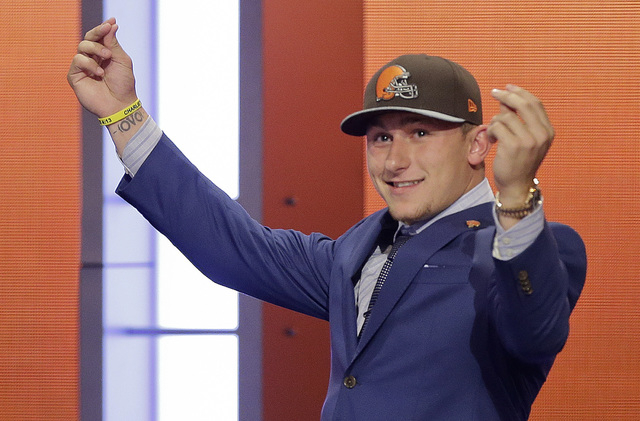 Texas A&M quarterback Johnny Manziel reacts after being selected by the Cleveland Browns as the 22nd pick in the first round of the 2014 NFL Draft, Thursday, May 8, 2014, in New York. (AP Photo/Fr ...