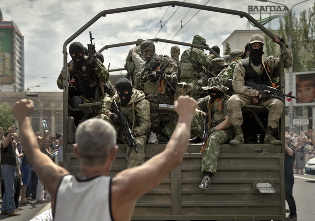 A man cheers as pro-Russian gunmen drive away in a truck in Lenin square in Donetsk, Ukraine, Sunday, May 25, 2014. A convoy of an armored personnel carrier and seven trucks carrying several hundr ...