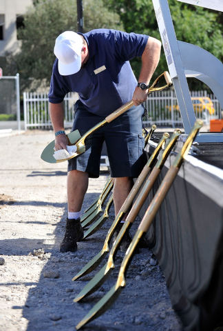 Chris Young, logistic supervisor for MGM Resorts Events polishes gold colored shovels before the start of a ceremonial ground breaking event for new MGM Resorts International and AEG joint venture ...