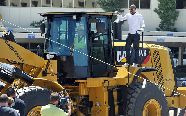 Boxer Floyd Mayweather Jr. arrives aboard a front end loader during a ceremonial ground breaking event for new MGM Resorts International and AEG joint venture indoor arena located behind the New Y ...