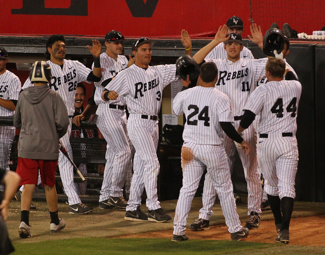 UNLV's A.J. Hernandez (24) and Morgan Stotts (44) celebrate their runs with teammates while playing against Fresno State in the fourth inning during a game in the Mountain West baseball tournament ...