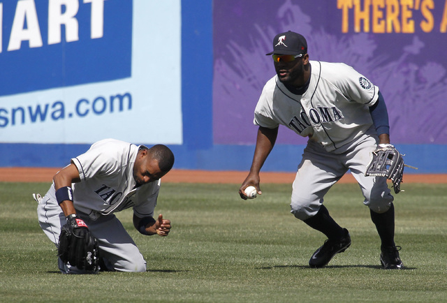 Tacoma Rainiers  outfielder Endy Chavez, left, lies on the ground dazed after missing a fly ball while centerfielder Abraham Almonte throws the ball into the infield in the sixth inning of the gam ...